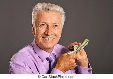 Close-up portrait of elderly man holding dollars