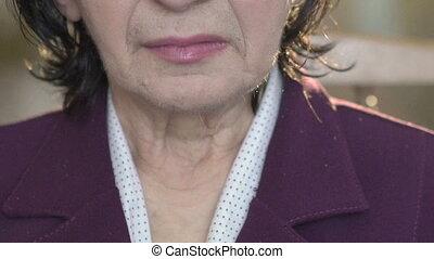 Close up portrait of elegant old woman's neck, face. Smiling. Slowly
