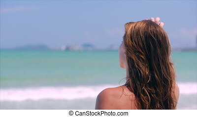 Close-Up Portrait of European Beautiful Cute Brunette Young Woman or Cheerful Girl Looking Towards the Sea, Running His Hand Over the Hair Blowing in the Wind on a Tropical Beach, Slow Motion.