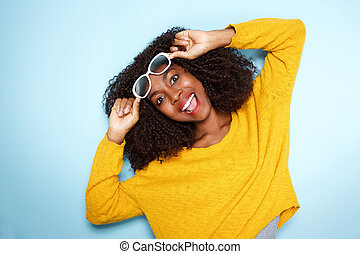 excited young african female in sunglasses on blue background