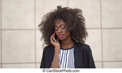 Close-up portrait of fabulous and confident african american woman talking by phone on the white textured wall background