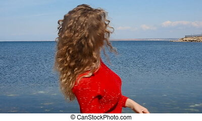 Close up portrait of fashion trendy woman running hand through curly hair blowing in wind by sea on beach. Happy female over blue sky