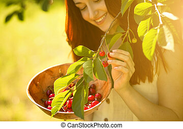Close up portrait of ginger beautiful girl picking cherries.