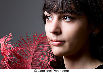 Close-up portrait of girl with red feathers.