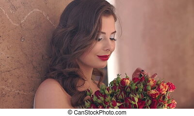 Close-up portrait of gorgeous girl with a bouquet of autumn flowers in the Park.