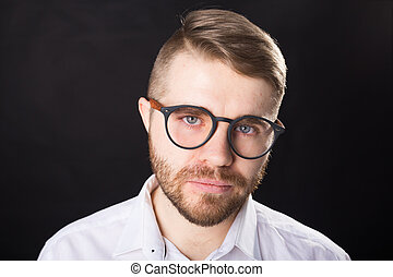 Close up portrait of handsome bearded man in stylish glasses standing against black wall