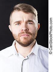 Close up portrait of handsome serious bearded man standing against black wall