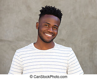 happy african man with beard smiling by wall