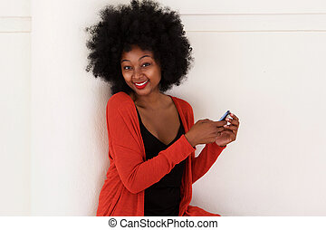happy african woman with mobile phone by white wall