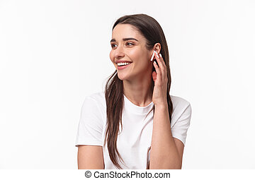 Close-up portrait of happy charming young woman with long hair, looking away smiling and laughing joyfully, changing song touching her wireless earbud, stand white background