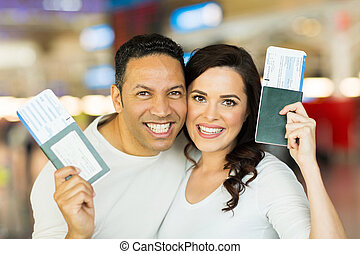 couple holding passport and boarding pass - close up...