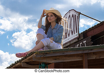 close up portrait of happy cowgirl on roof holding hat