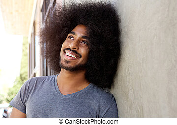 happy fashionable man with afro leaning against wall