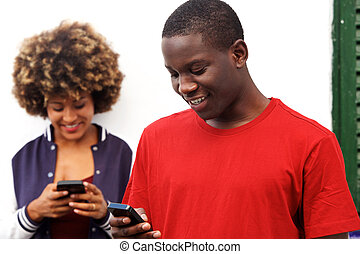 happy man and woman using cell phones outdoors