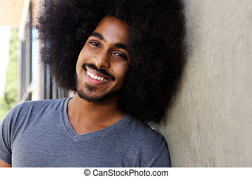 happy man with beard and afro leaning on wall