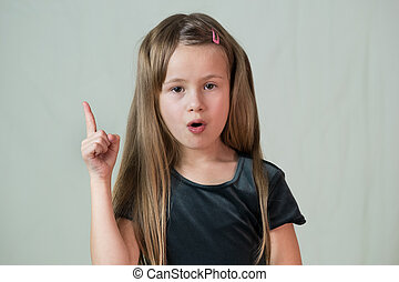 Close-up portrait of happy smiling little girl with long hair holding her finger up having an idea.