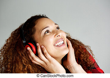 happy young african american woman listening to music with headphones and looking up