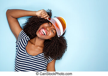 happy young african american woman wearing cap on blue background
