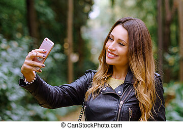 Close up portrait of happy young woman smiling and taking selfie while standing on blurred background park