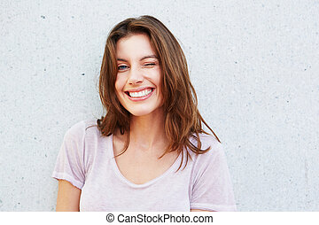 happy young woman smiling and winking against gray wall