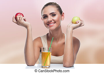Close-up portrait of happy young woman with apple on autmn color background. Concept vegetarian dieting - healthy food