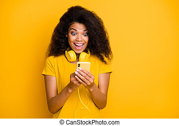 Close-up portrait of her she nice attractive glad amazed cheerful cheery wavy-haired girl browsing blog smm reading post listening hit isolated over bright vivid shine vibrant yellow color background