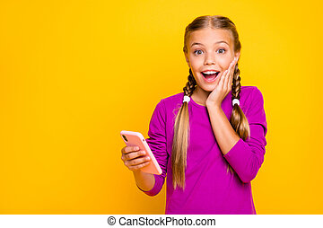 Close-up portrait of her she nice attractive lovely cute cheerful cheery amazed glad girl using digital device good news isolated over bright vivid shine vibrant yellow color background