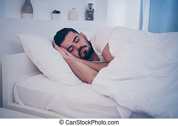 Close-up portrait of his he nice attractive peaceful brunette guy lying on white bed resting fallen asleep sleeping time at night late evening home hotel room flat indoors