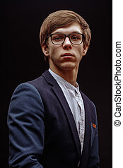close up portrait of intelligent young man in glasses looking at the camera