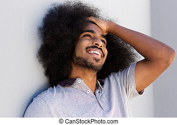 laughing afro man with hand in hair looking away