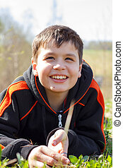 Close-up portrait of laughing boy lying on the grass