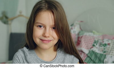 Close-up portrait of little cute girl looking at the camera and smiling kindly in bedroom at home