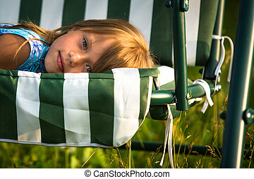 Close-up portrait of little girl lying on a swing in the yard of a country house