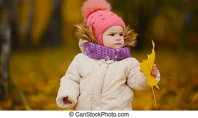 Close-up portrait of little girl standing with a maple leaf and looking at the camera smiling and talking to mom.