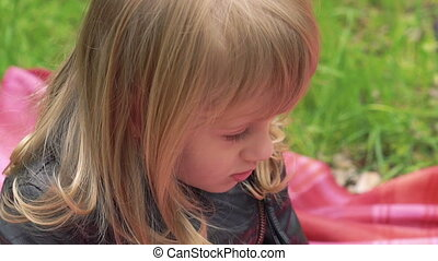 Close up portrait of little girl sincerely smiling on a lawn. Slowly