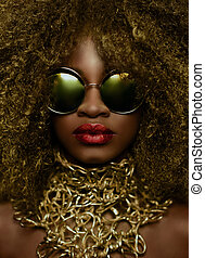 Close-up portrait of magic golden african american female model in massive sunglasses with bright glitter makeup, glossy hairstyle and big red lips. Studio shoot
