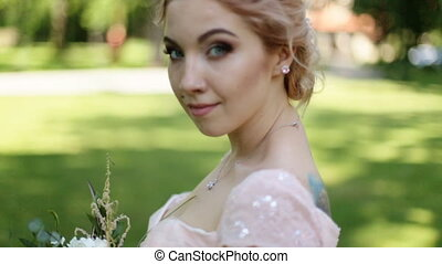 Close up portrait of magical beautiful young bride in elegant dress with bouquet in the park.