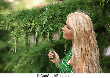 Close-up portrait of magnificent caucasian blond girl with natural makeup and long healthy wavy hair. Lovable long-haired blonde woman enjoying life over green fir tree brunch close up.