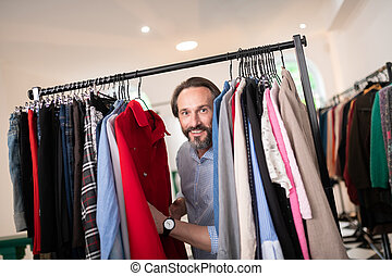 Close-up portrait of male pushing clothes in the clothing store.