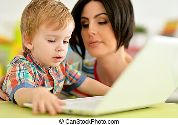 Close up portrait of mother and son using laptop together