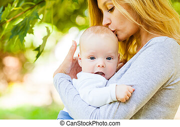 Close up portrait of mother kissing her infant baby