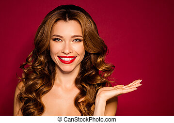 Close-up portrait of nice fascinating attractive cheerful confident wavy-haired girl holding on palm invisible object isolated bright vivid shine vibrant red maroon burgundy marsala color background