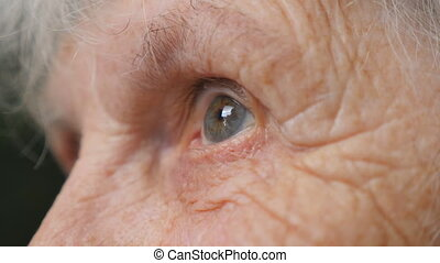 Close up portrait of old woman looking up. Eyes of an elderly lady with wrinkles around them. Side view Slow motion