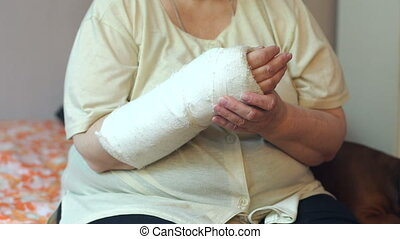 Close-up portrait of old woman with broken arm, her hand in a cast.