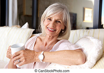 older woman sitting on couch with coffee