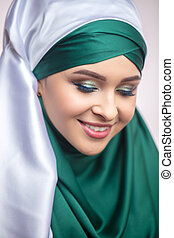 close up portrait of pleasant model in hijab looking down