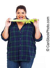 plus size teenage girl eating celery