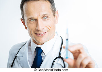 Close up portrait of practitioner looking at syringe