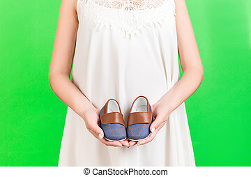 Close up portrait of pregnant woman in white dress holding booties for baby boy at green background. Happy child expecting. Copy space