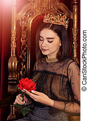 Close up portrait of queen sitting on throne with flower